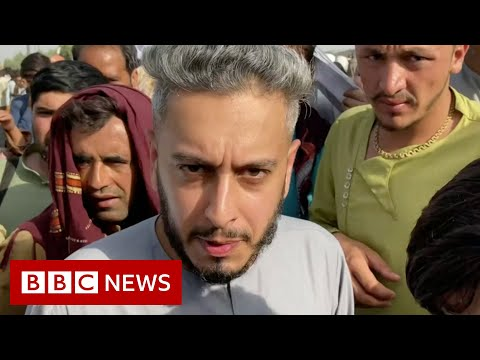 BBC surrounded by people showing papers at Kabul airport - BBC News
